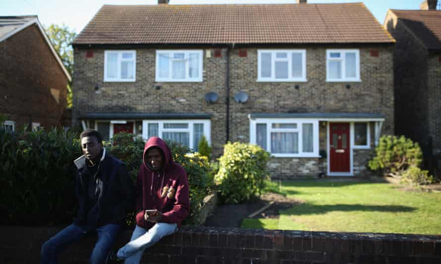 A group of young asylum seekers from Sudan sit on a wall outside their temporary housing in Longford, England