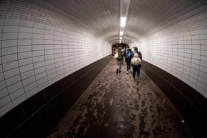 People walk through a tunnel at a station in L'Haÿ-les-Roses, France