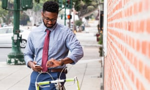 Young man standing beside bicycle, using smartphone, looking at wristwatch