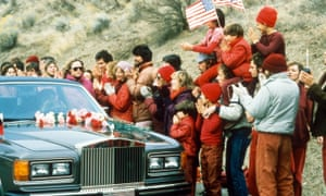 Rajneesh is greeted by followers as he enters the commune in a Rolls-Royce.