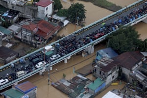Vehicles are parked on a bridge to avoid floodwaters in Metro Manila