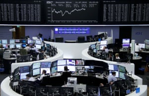 Traders working at their desks in front of the German share price index, DAX board, at the stock exchange in Frankfurt, Germany, today.
