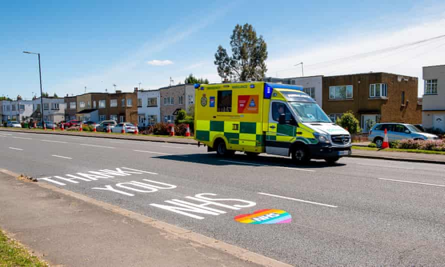 An ambulance drives past a thank you NHS sign painted on the road
