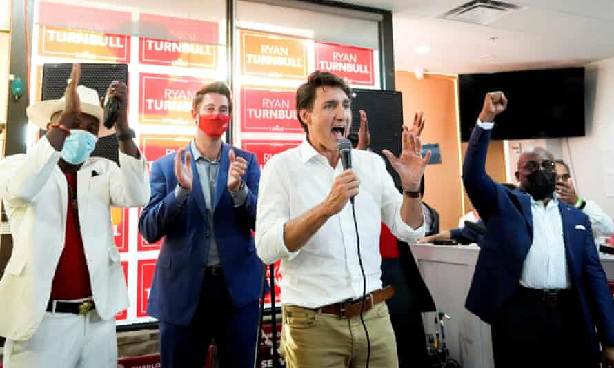 Justin Trudeau speaking animatedly at an event with other people on the podium applauding.