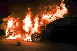 New York, US Two vehicles burn next to a box of spent fireworks in the Bedford-Stuyvesant neighbourhood of Brooklyn