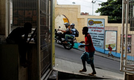 People walk past shops in the Alemão favela complex whose residents face new challenges including the closure of a health clinic and cable car service, as well as routine gunfights between drug gangs and police.