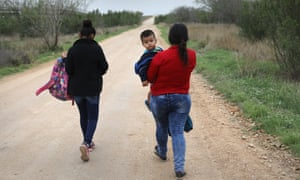 Central American migrants walk after crossing the US-Mexico border to turn themselves into border patrol agents near McAllen, Texas.