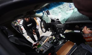 Protestors looks through a destroyed police car.