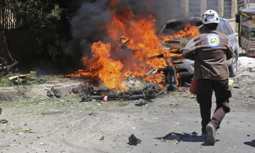 Civil defence workers extinguish a burning car in Idlib, Syria.