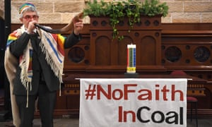 Rabbi Jonathan Keren-Black uses a rabbinical horn (shofar) to sound the end of the era of coal