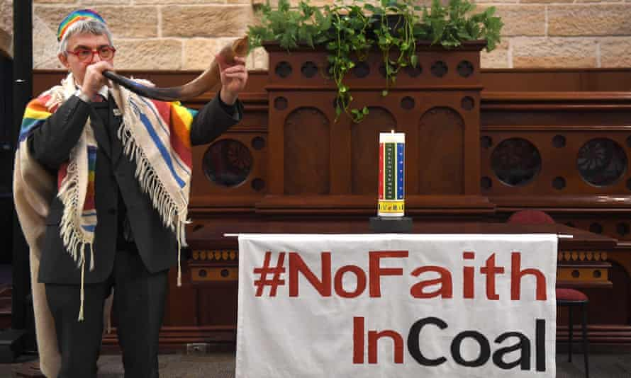 Rabbi Jonathan Keren-Black uses a rabbinical horn (shofar) to sound the end of the era of coal