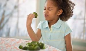 kid eats broccoli