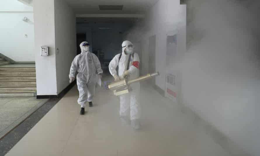 Volunteers in protective suits disinfect a residential compound in Wuhan on Sunday.
