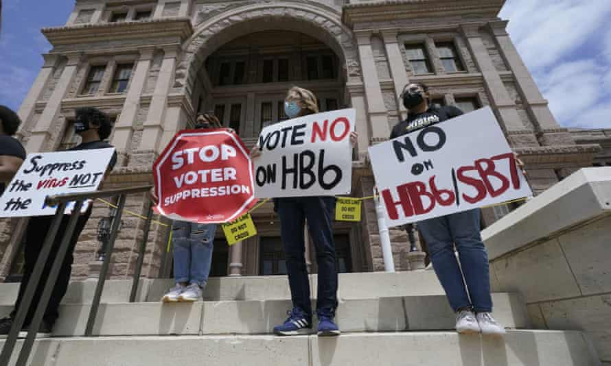 People opposed to Texas voter bills HB6 and SB7 hold signs on the steps of the state capitol in Austin on 21 April.