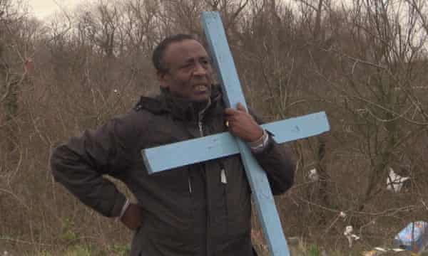 Ethiopian pastor Rev Teferi Shuremo watches as his church is destroyed at a migrant camp in Calais