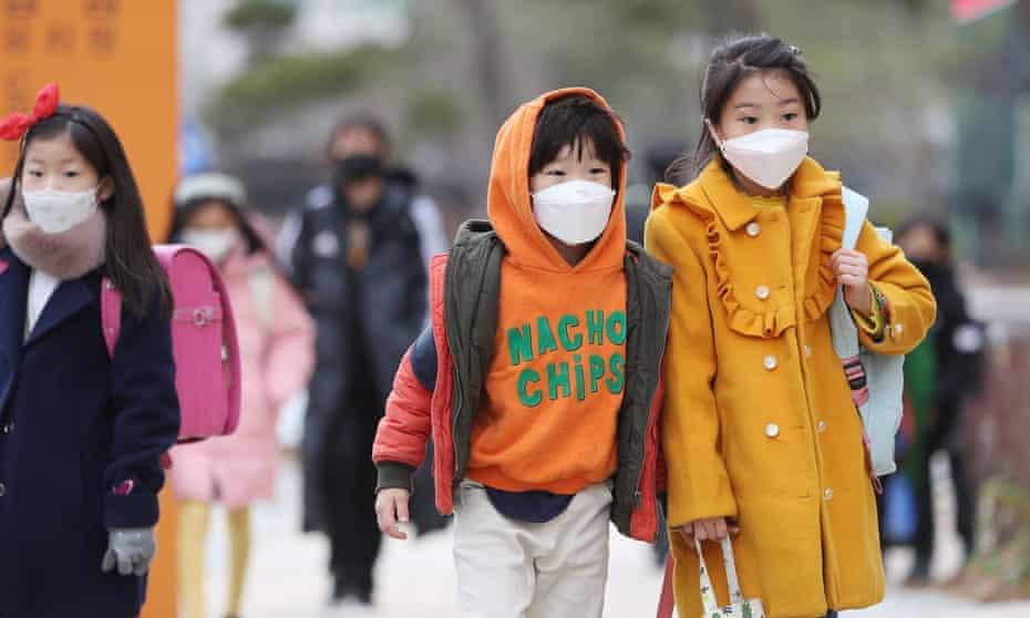 Children wear masks as they head to school in Sejong, South Korea.