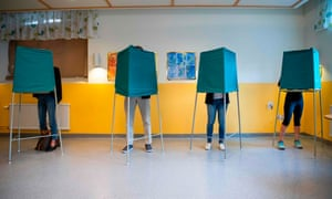 People cast their votes in booths at a polling station in Stockholm.