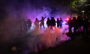 Federal agents fire teargas at protesters near the federal courthouse in Portland, Oregon, on 23 July.