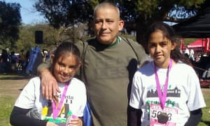 Rómulo Avelica-González with his daughters Yuleni, left, and Fatima, right, and their running medals.