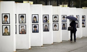 A woman looks at images of the victims of the sunken ferry Sewol at a memorial in Ansan.