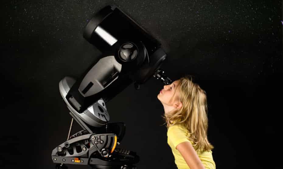 Young girl looking through a telescope
