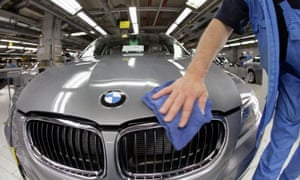 A worker cleans the hood of a BMW 3-series