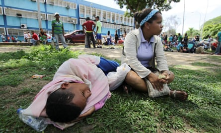 People wait outside a health centre in San Felix, Venezuela, as they wait to get treatment for malaria.