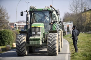 An Italian police officer talks to a farmer on a tractor at a road block in Zorlesco, northern Italy.