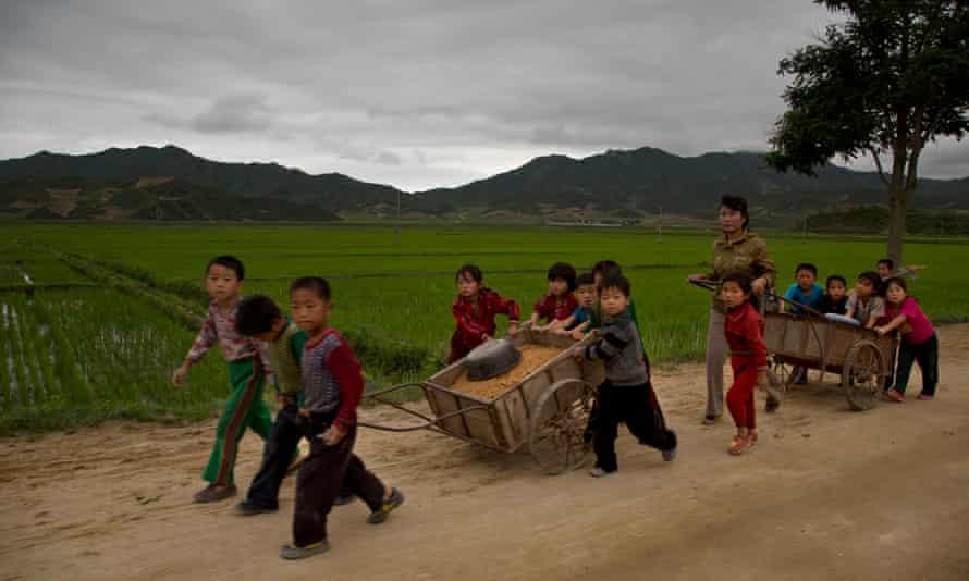Young North Korean schoolchildren help to fix pot holes in a rural road in North Korea's North Hamgyong province