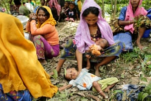 Rohingya refugees sit under trees in a forest during hot weather in Ukhiya, Cox's Bazar, Bangladesh.