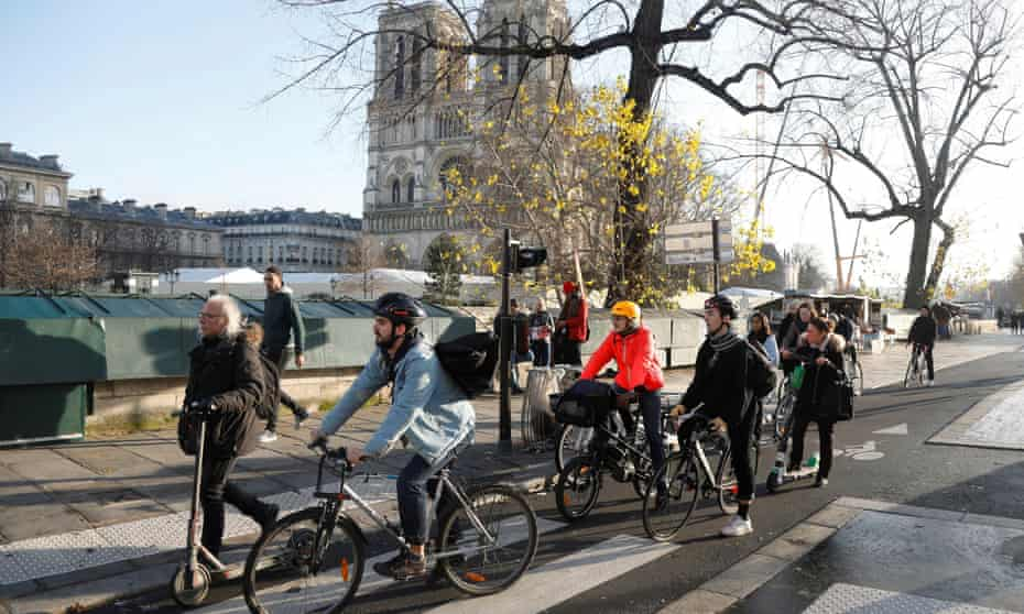 Commuters on bicycles and scooters near Notre Dame Cathedral.