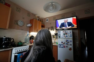 A woman in in St. Petersburg watches Russian President Vladimir Putin televised address to the nation