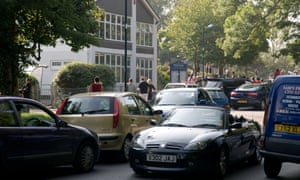 Cars queue to collect children outside a primary school in Aberystwyth, Wales