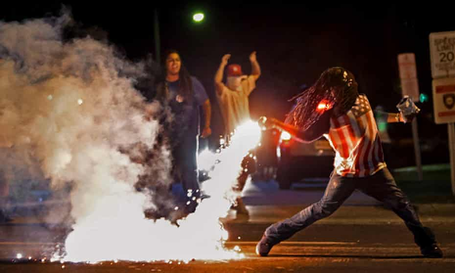 Protesters throw back a tear gas canister fired by police in Ferguson, Missouri, on 13 August 2014.