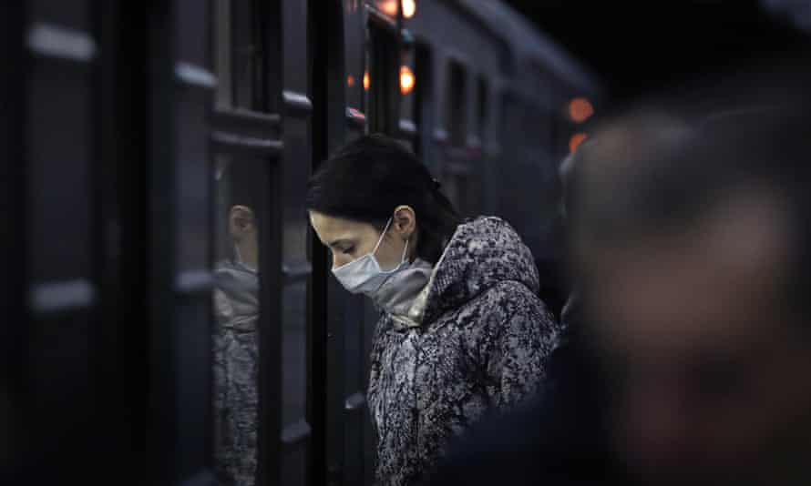 A woman in a face mask prepares to board a train