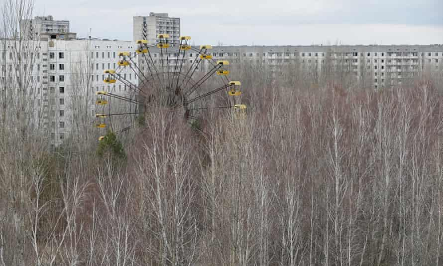 A view across overgrown trees and an unused big wheel to the abandoned town of Pripyat.