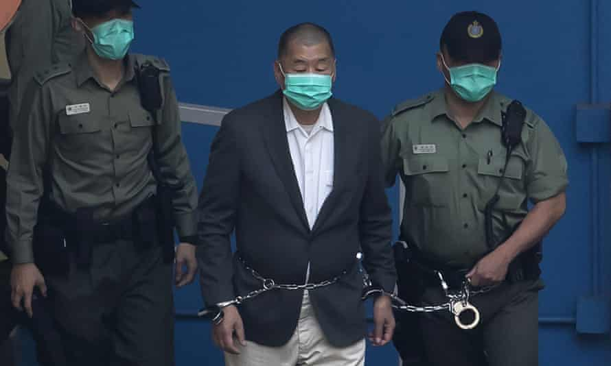 Jimmy Lai in chains an handcuffs, escorted by two police officers.