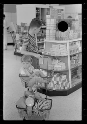 A boy and a younger child with shopping trolley  and basket in a store.