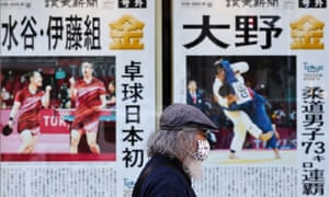 A man wearing a protective mask walks past a display of a newspaper reporting the Tokyo 2020 Olympic Games.
