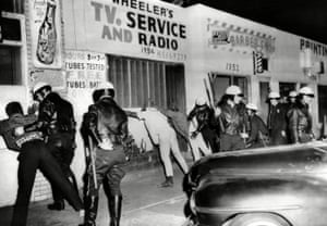 Police search African American youths in 1966.