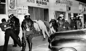 Police search African American youths during the Watts riots
