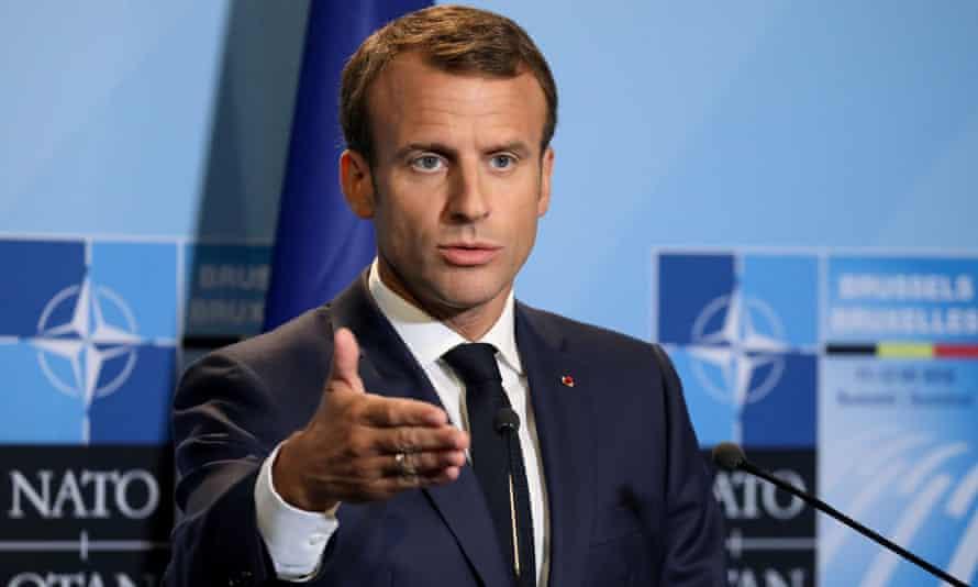 Emmanuel Macron with Nato logo behind him