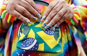 Hands with long fingernails hold a Brazilian flag purse