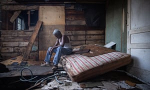 Theophilus Charles, 70, sits inside his house in Houma, Louisiana, which was heavily damaged by the storm