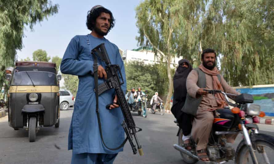 A young bearded man in a blue outfit with an assault rifle stands in the middle of traffic