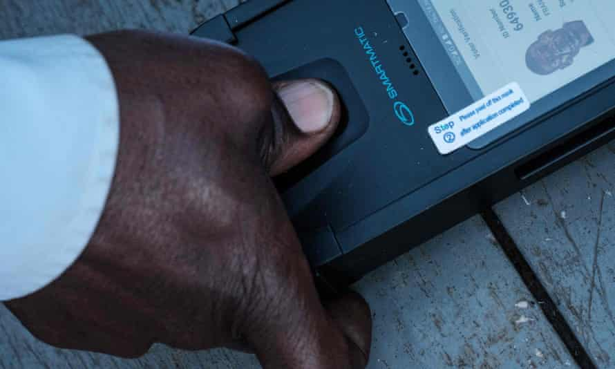 A man puts his thumb into a biometric machine to verify his identification and cast his vote at a polling station in Kampala, Uganda.