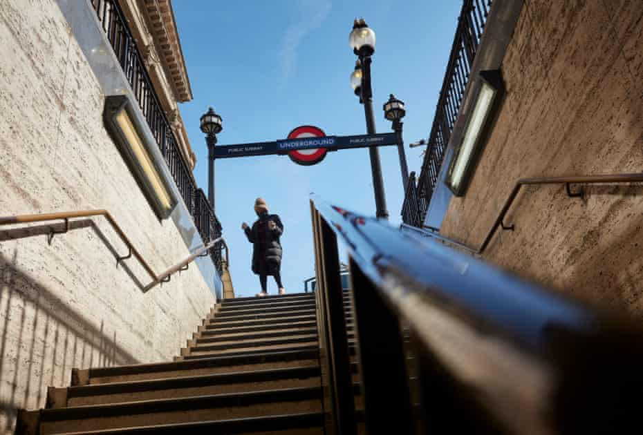 A woman stands at the top of the stairs at Piccadilly Circus station, afraid to touch the railings.