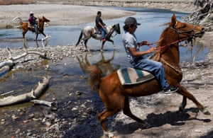 Fort Laramie treaty riders return from crossing a creek in the tribal area on the grounds of the Fort Laramie