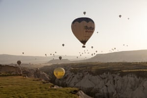 Hot air balloons crowding over valley in sunlight
