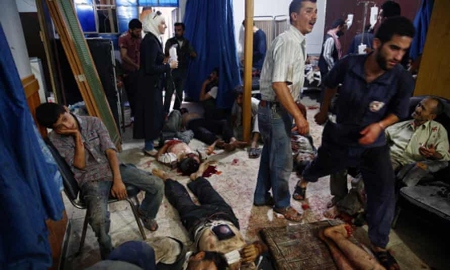 People wounded in Syria market attack receive treatment at a makeshift hospital in Douma.